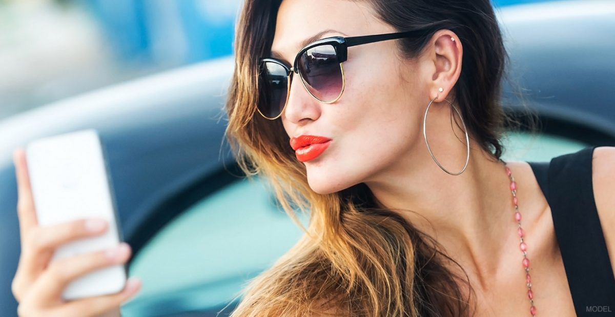 Woman with sunglasses and bright lipstick holding her phone
