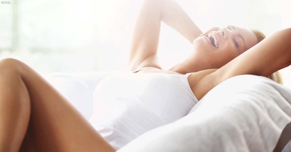 Woman lying on bed and smiling after her breast augmentation